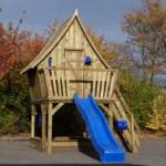Groot speelhuis van geïmpregneerd hout met een lange glijbaan