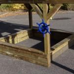 Onder het speelhuis is een ruime zandbak met zitplankjes