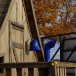 Houten speelhuis met balkon.