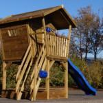 Groot houten speelhuis met glijbaan