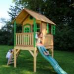 Houten speelhuis met glijbaan voor in de tuin