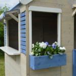 Leuk houten speelhuisje voorzien van zonneschermpjes en bloembakje