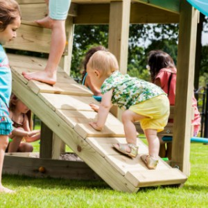 Houten klimwand van een speeltoestel voor buiten, gemonteerd aan een speeltoren van GrootPlezier.
