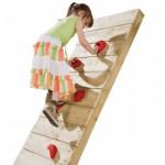 Meisje dat klimt op klimwand van speeltoren met klimstenen