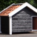 Een mooi hondenhok, de zwart/witte kleurstelling maakt dit hondenhok zeer stijlvol, de oranje dakpannen geven het hok een frisse kleur.