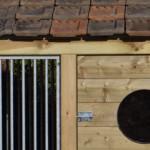 Verduurzaamd hout, gegalvaniseerd traliewerk, dakpannen en plexiglas.